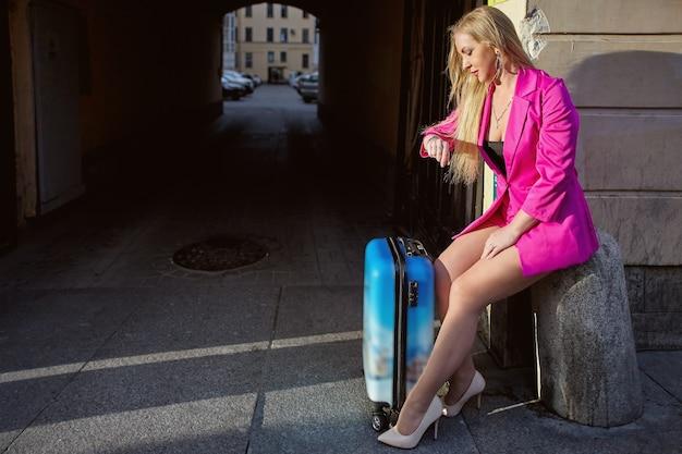 Frau schaut auf ihre uhr, während sie auf taxi wartet und vor einem wohnhaus auf stadtstraße sitzt.