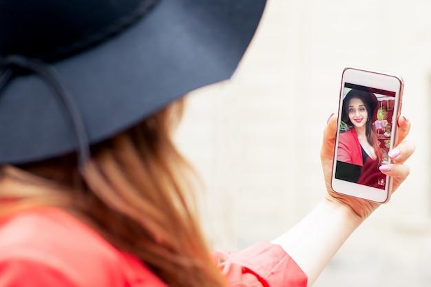 Frau schaut auf ihrem smartphone, während sie online spricht.