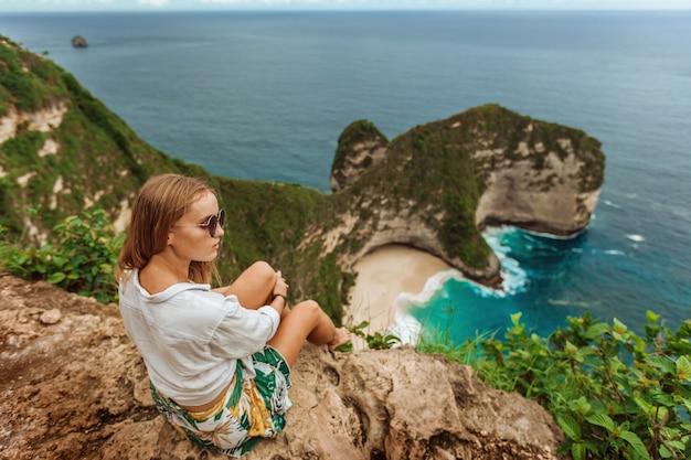 Frau schaut auf kelingking beach auf nusa penida bali indonesien