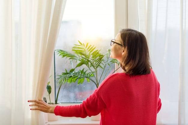 Frau schaut aus dem fenster, öffnet die vorhänge