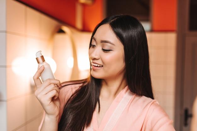 Frau schaut gesichtscreme mit lächeln an und posiert im badezimmer