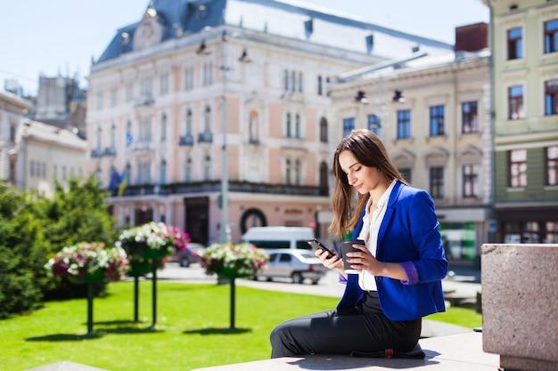 Frau schaut ihr telefon sitzt mit tasse kaffee auf der straße