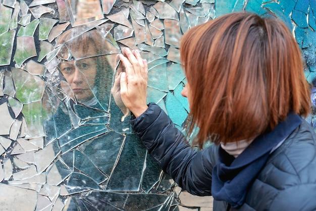 Frau schaut in einen zerbrochenen spiegel und zeigt ihre hand auf einem spiegel. internationaler tag zur beseitigung von gewalt gegen frauen