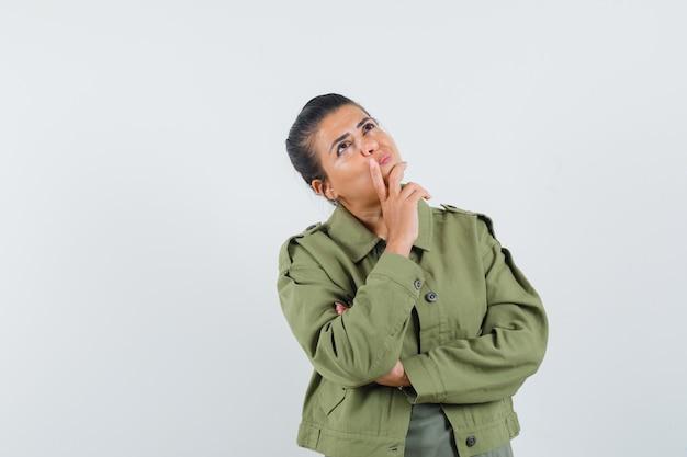 Frau schaut in jacke, t-shirt und nachdenklich