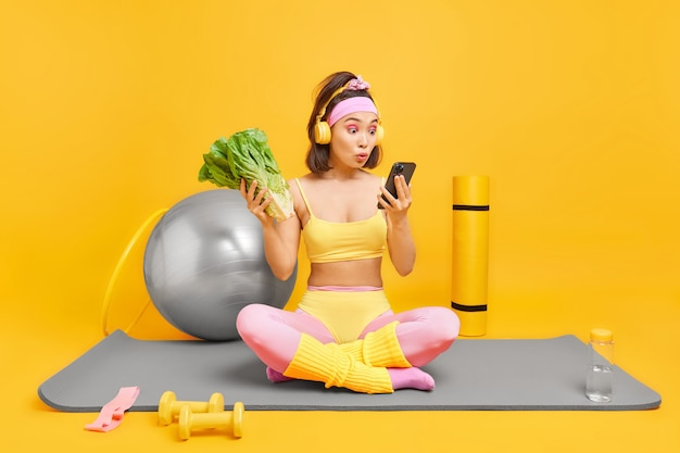 Frau schaut schockiert auf das smartphone-display sitzt mit gekreuzten beinen auf der fitnessmatte wählt lied aus der playlist führt aktiven lebensstil hält sich an gesunde ernährungsposen im fitnessstudio zu hause