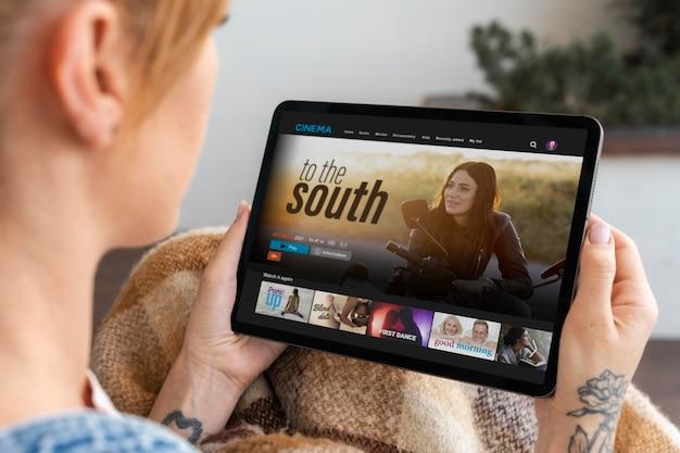 Frau schaut sich auf ihrem tablet einen film an