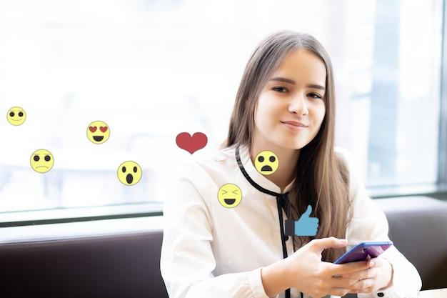Frau schaut sich soziale medien an und sendet emojis