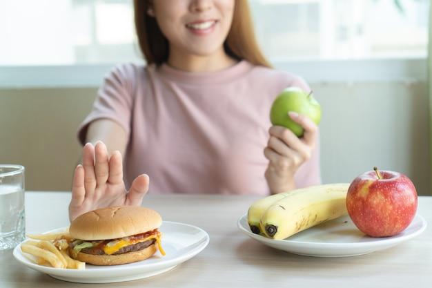 Frau schieben fastfood weg und wählen apfel