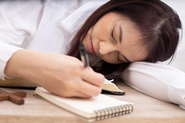 Frau schläft am arbeitsplatz. müde frau schläft im bett