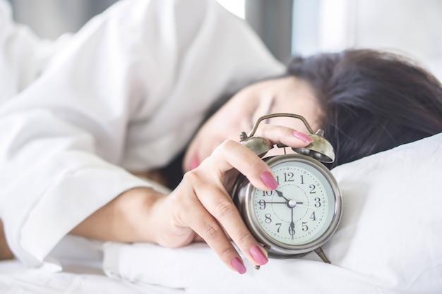 Frau schläft auf dem bett hand wecker ausschalten