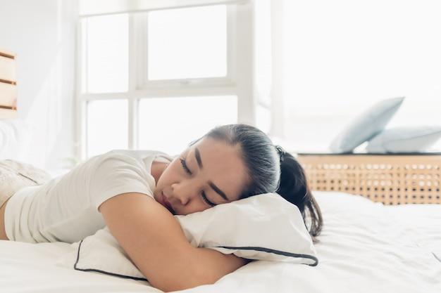 Frau schläft auf ihrem weißen bett in der wohnung.