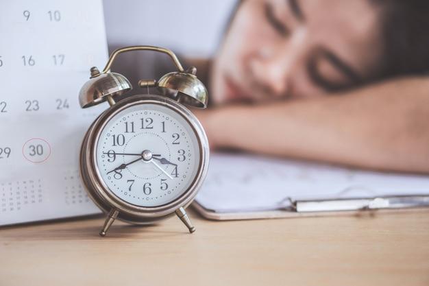 Frau schläft bei der arbeit mit stichtag kalender und uhr