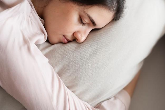 Frau schläft bequem auf ihrem kissen Kostenlose Fotos