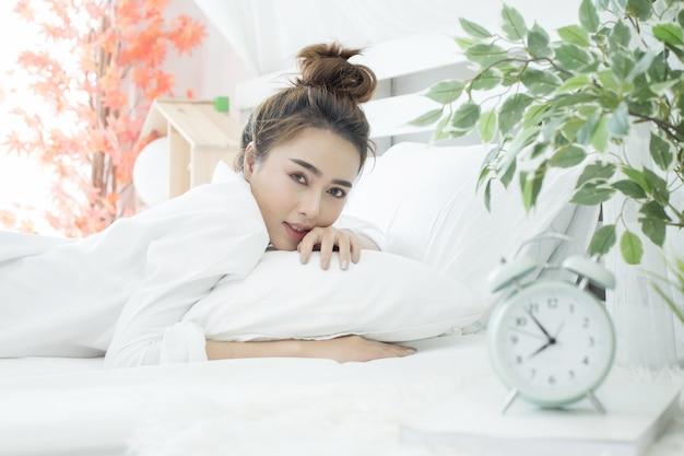 Frau schläft im bett, während ihr wecker die frühe zeit zu hause im schlafzimmer zeigt