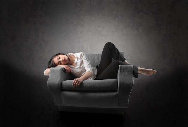 Frau schläft in einem sessel