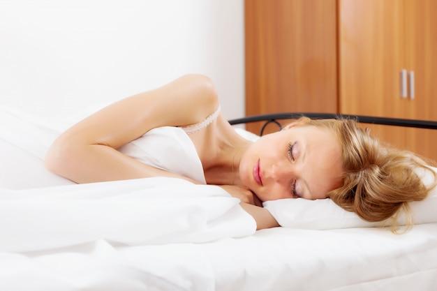 Frau schläft in ihrem bett