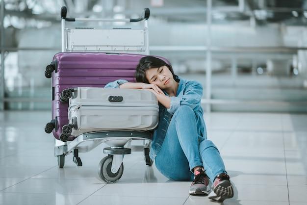 Frau schläft mit gepäckwagen am flughafen