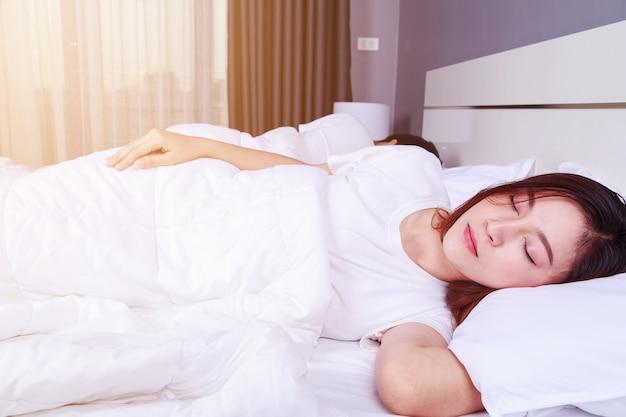 Frau schläft mit ihrem ehemann in einem bequemen bett zu hause