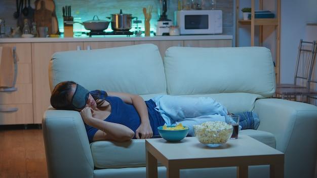 Frau schläft mit schlafmaske im wohnzimmer während der fernsehsendung. müde, erschöpfte, einsame, schläfrige dame im schlafanzug, die auf einem gemütlichen sofa vor dem fernseher einschläft, die augen schließt, während sie nachts einen film sieht.
