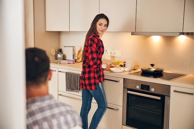 Frau schlägt eier für ein omelett in einer schüssel