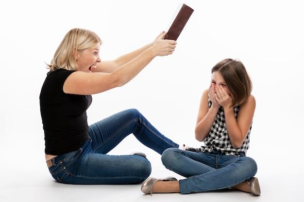 Frau schlägt teenager-tochter mit einem schweren buch. beziehungen in der familie und die schwierigkeiten des fernunterrichts zu hause während der isolationsphase. weiße wand.