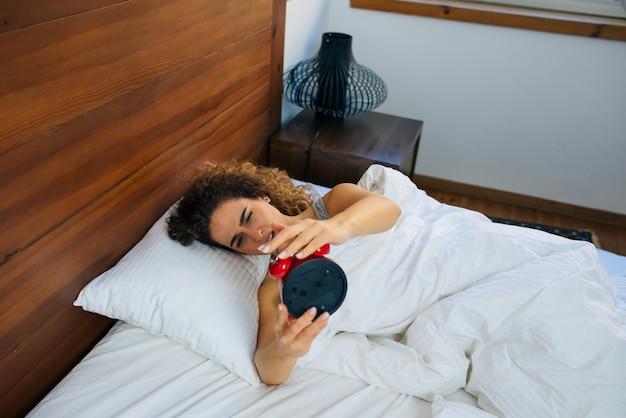Frau schlafen und aufwachen, um den wecker am morgen auszuschalten.