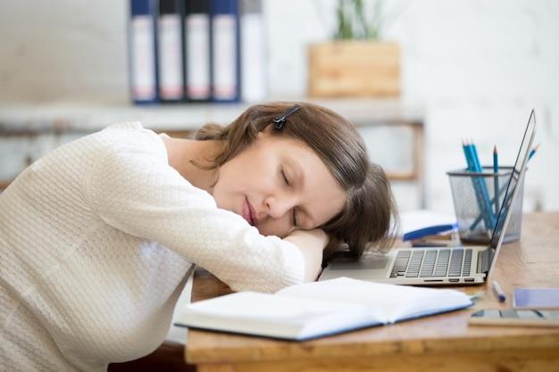 Frau schlafend auf dem schreibtisch