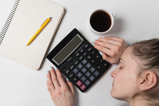 Frau schlief neben taschenrechner und heft ein. budgetplanung, berichterstellung. draufsicht