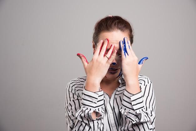 Frau schloss ihr gesicht mit malt hände auf grauem hintergrund