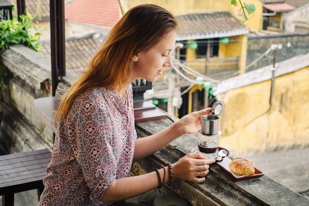 Frau schmeckt vietnamesischen kaffee