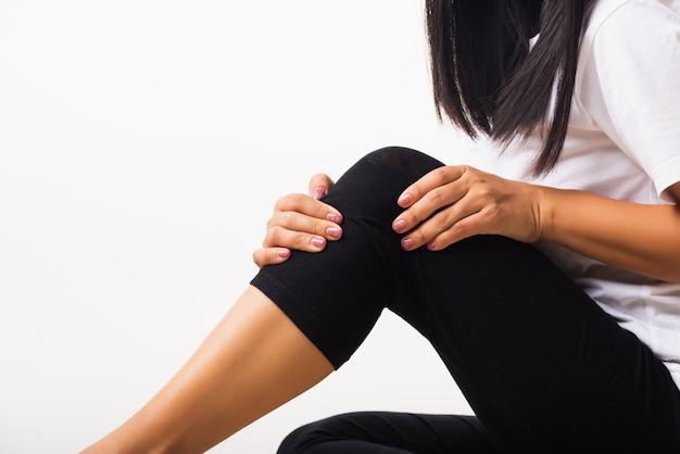 Frau schmerzen knie und sie verwendet handgelenk halten knie qual
