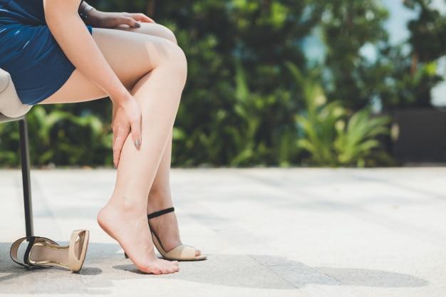 Frau schmerzt vom tragen von schuhen des hohen absatzes
