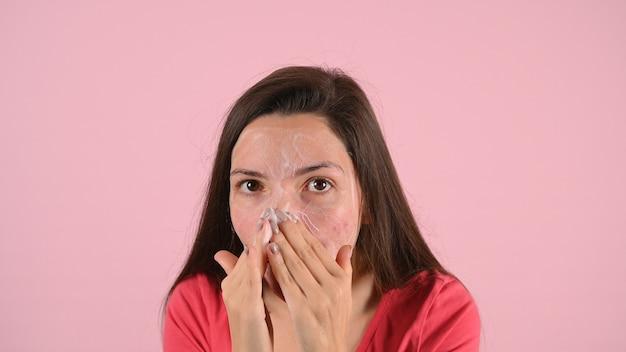 Frau schmiert ihr gesicht mit akne-creme