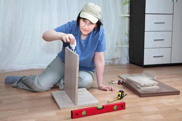 Frau schmiert oberfläche der klebenden spanplatte während der möbelmontage.