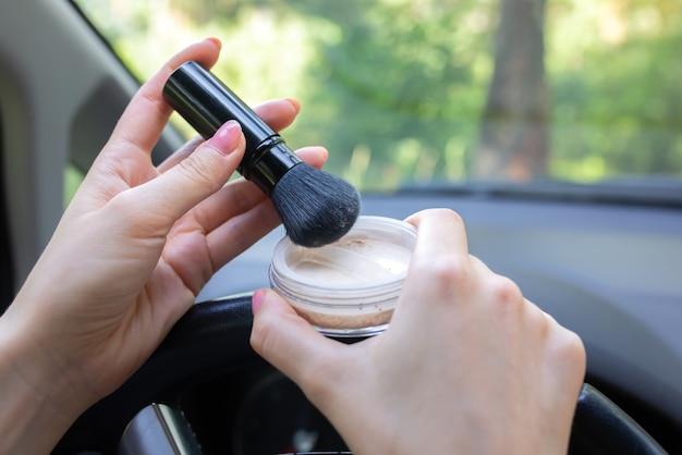Frau schminkt sich im auto. mädchen mit gesichtspuder hinter dem steuer. gefährliche situation auf der straße. möglichkeit eines unfalls.