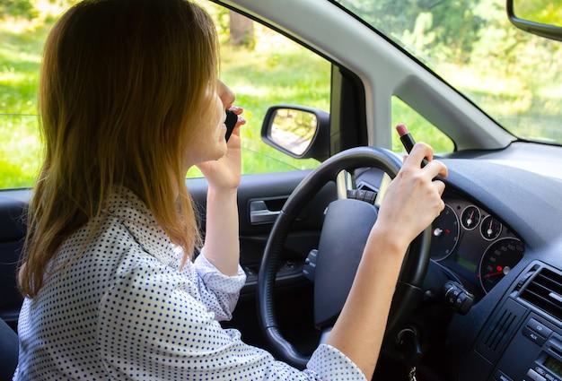 Frau schminkt sich im auto. mädchen mit lippenstift hinter dem rad am telefon sprechen. gefährliche situation auf der straße. möglichkeit eines unfalls.