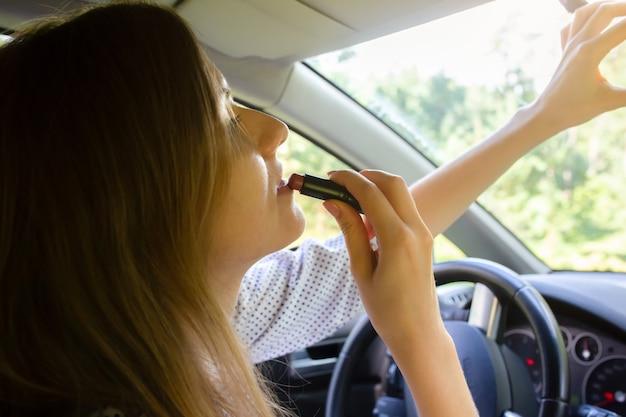 Frau schminkt sich im auto. mädchen mit lippenstift hinter dem steuer. gefährliche situation auf der straße. möglichkeit eines unfalls.