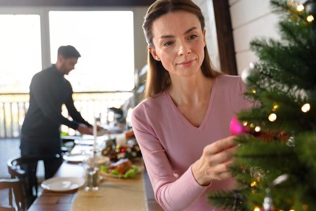 Frau schmückt den weihnachtsbaum neben ihrem mann