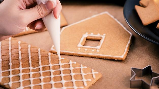 Frau schmückt lebkuchenhaus mit weißem zuckerguss auf holztischhintergrund, backpapier in der küche, nahaufnahme, makro.