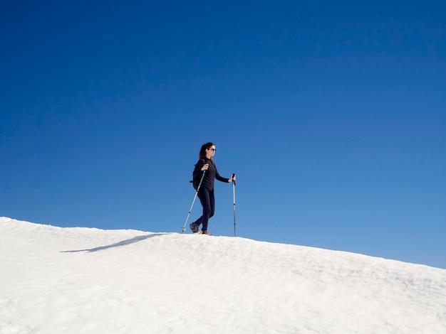 Frau schneeschuhwandern in san isidro, león, spanien an einem sonnigen tag