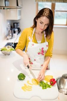 Frau schneiden von gemüse auf schneidebrett