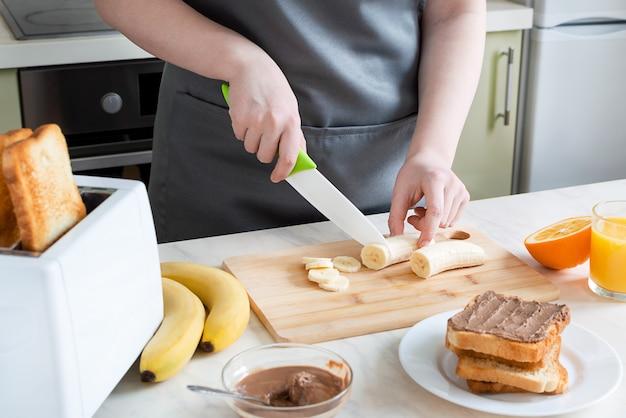 Frau schneidet banane für toast zum frühstück. europäisches frühstück mit toast, banane und saft.