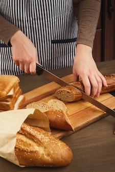 Frau schneidet brot auf holzbrett. unerkennbare köchin, die gesunde sandwiches zubereitet, seitenansicht, kopierraum