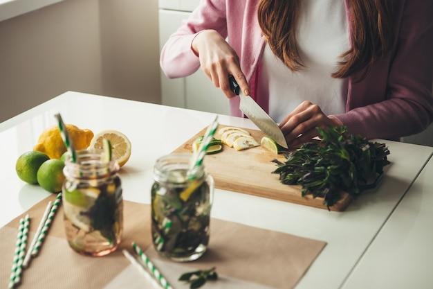 Frau schneidet früchte für die herstellung eines mojito-getränks zu hause mit zitronen und minze im glas