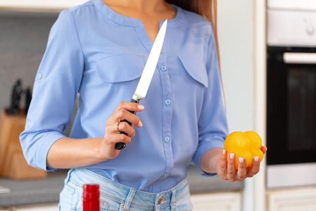 Frau schneidet gelbe paprika für salat auf holztisch