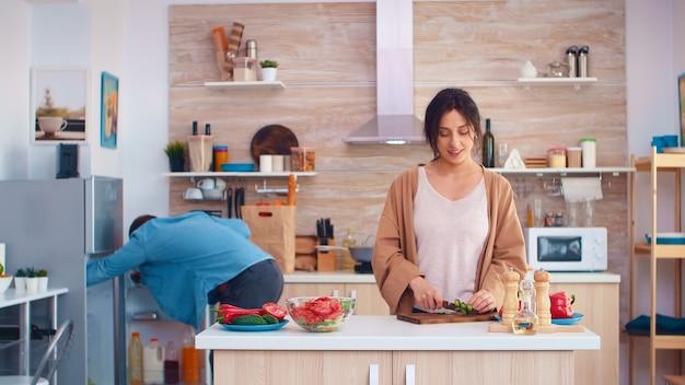 Frau schneidet gurken auf holzbrett für gesunden salat. ehemann, der kühlschrank öffnet. kochen, das gesundes bio-lebensmittel glücklich zusammen lebensstil zubereitet. fröhliches essen in der familie mit gemüse