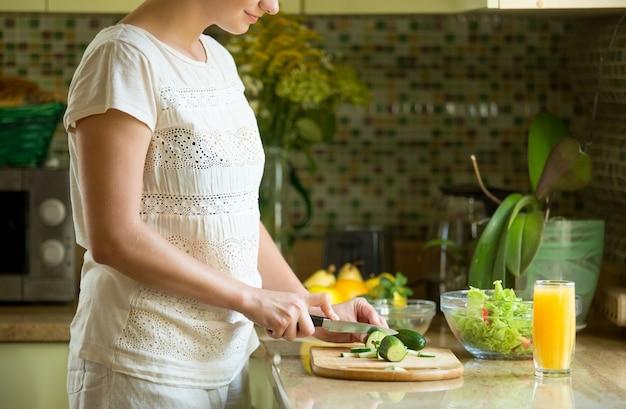 Frau schneidet gurken für einen salat auf der küche