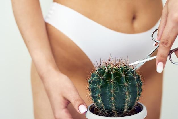 Frau schneidet kaktusdornen mit einer kleinen schere