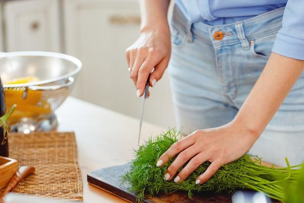 Frau schneidet petersilie auf holzbrett in der küche