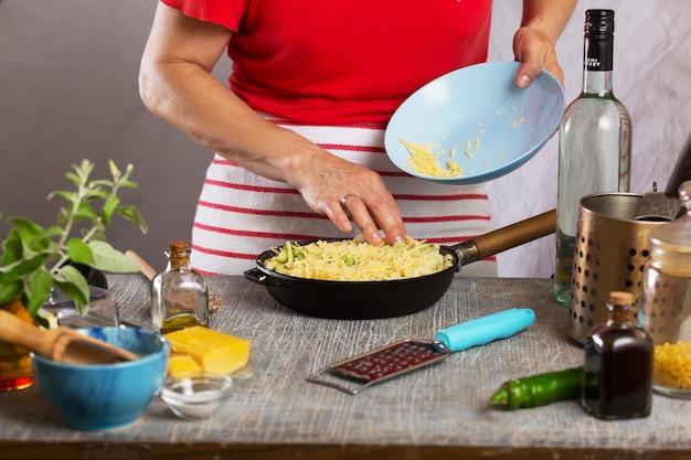 Frau schneidet reife wassermelone auf einem holztisch